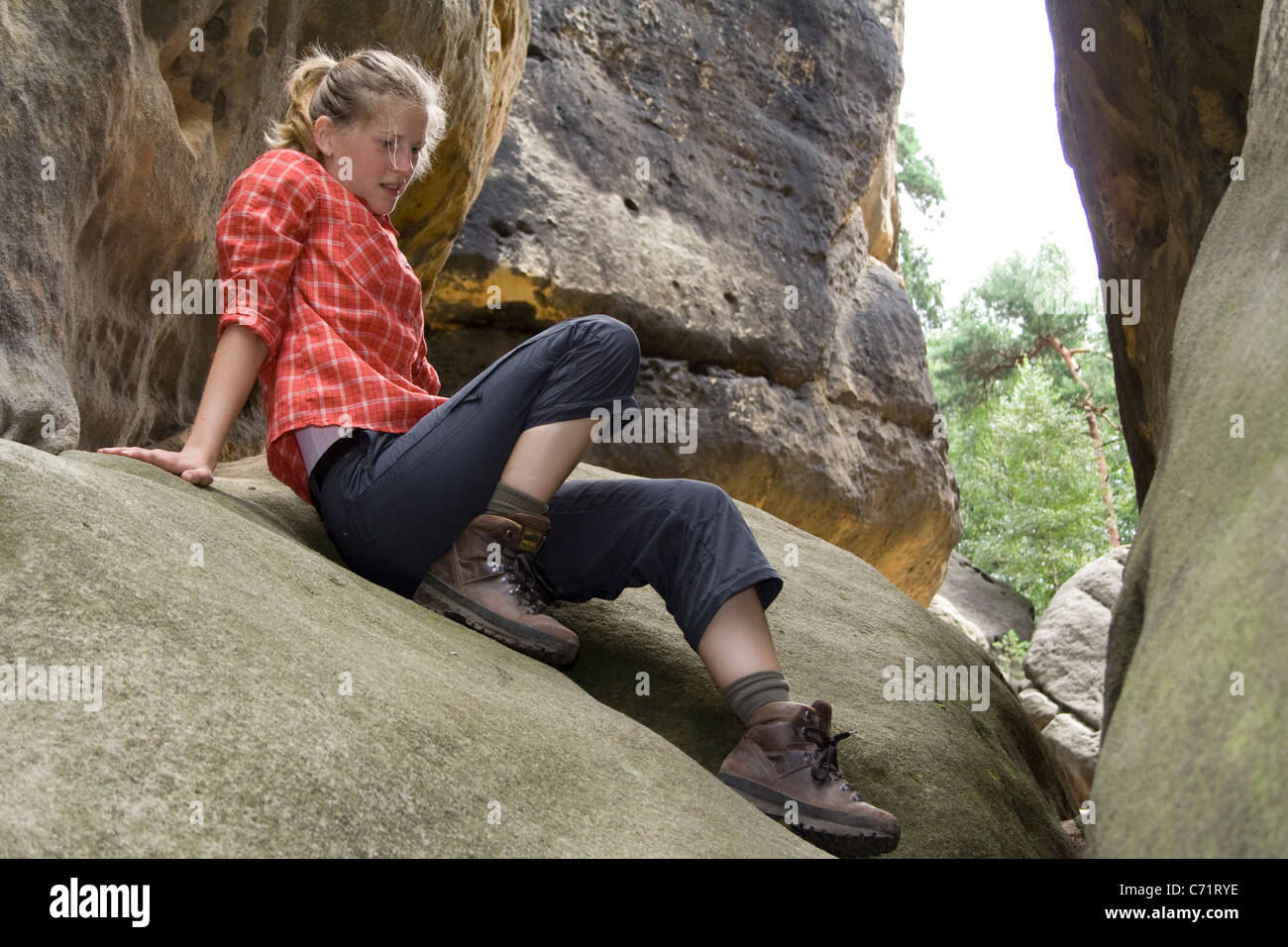 Woman taking a rest and looking dreamily at rocks after hiking through the Elbe Sandstone Mountains in Saxony, Germany, - Stock Image
