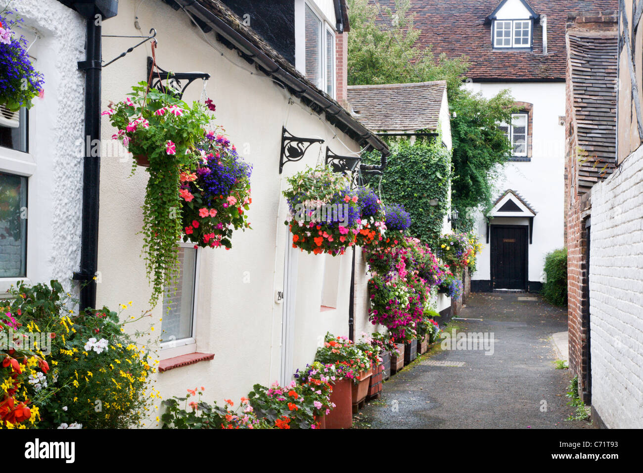 Hanging Baskets in an Alleyway Bridgnorth Shropshire England - Stock Image