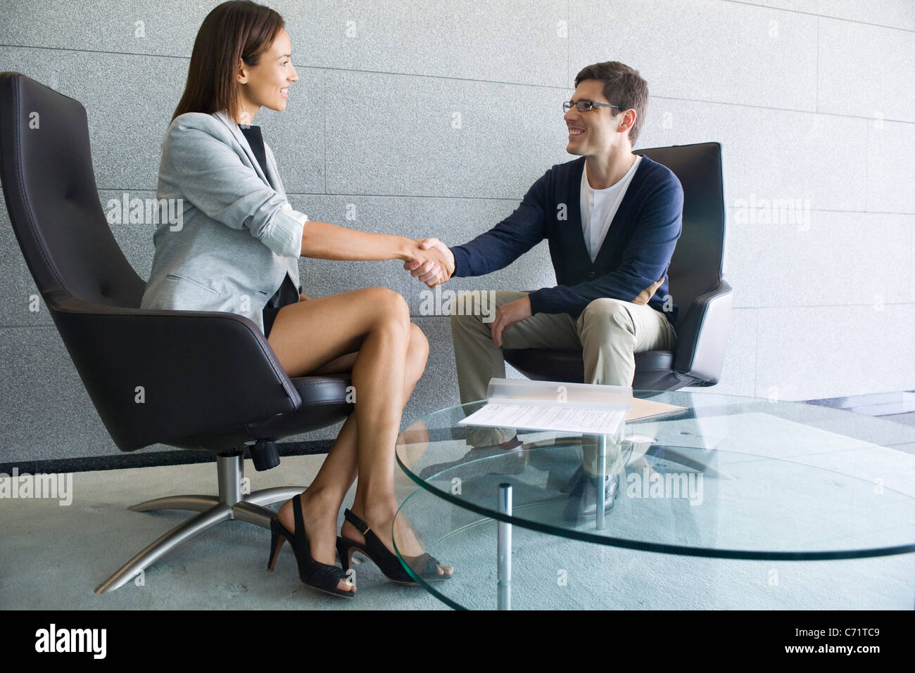 Businesswoman shaking hands with client - Stock Image