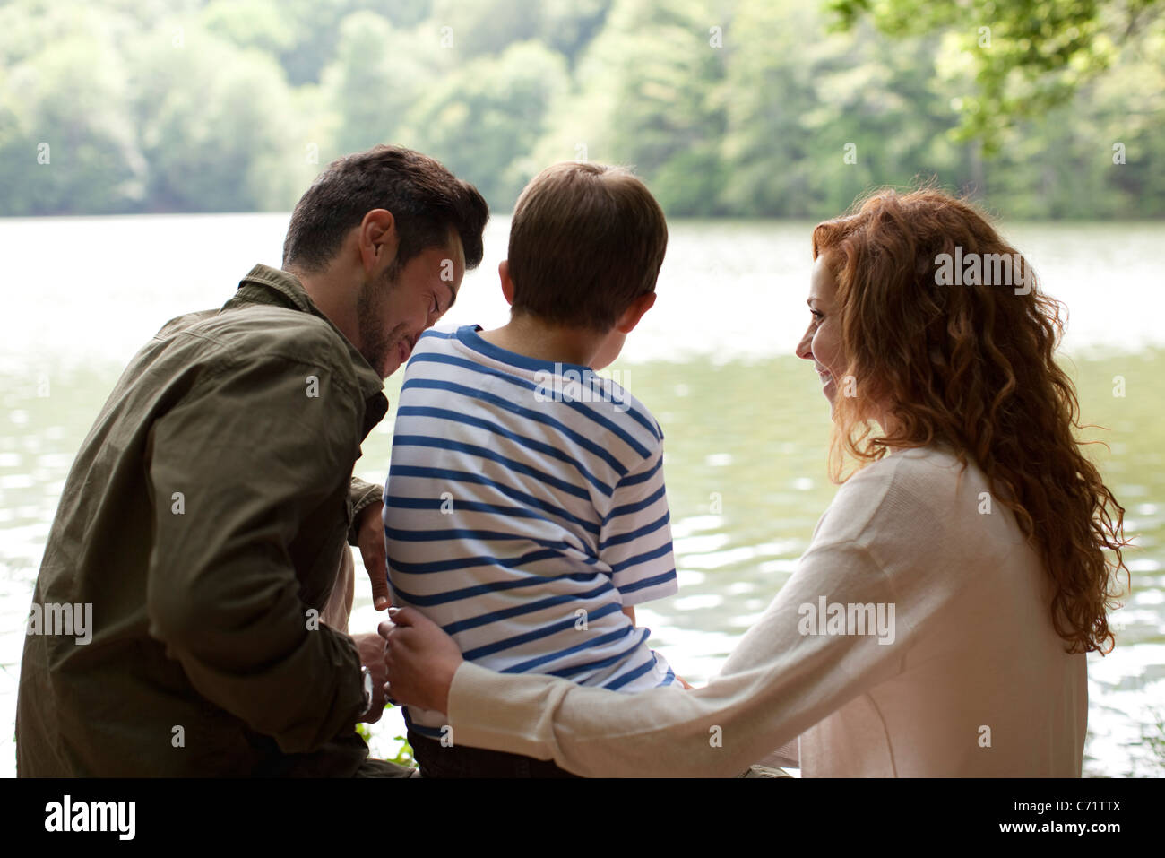 Family by lake, rear view - Stock Image