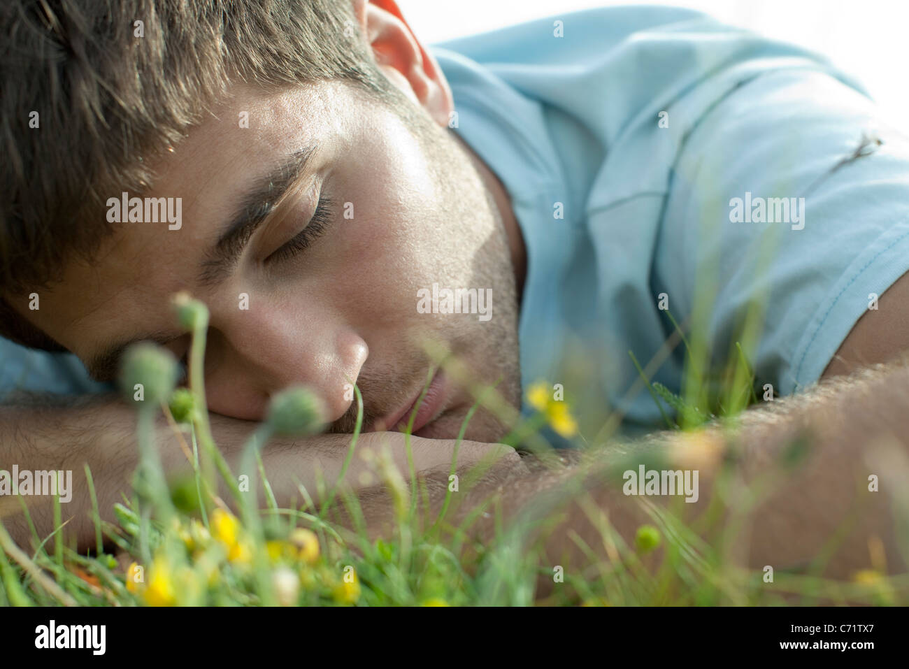 Man napping on meadow, close-up - Stock Image