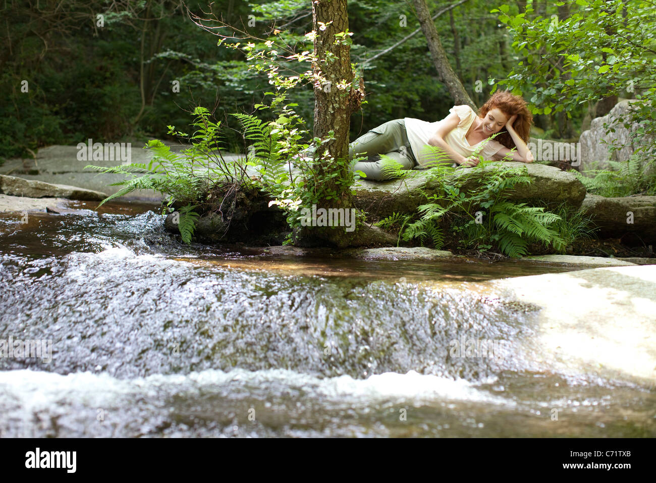 Young woman relaxing on rock by flowing stream - Stock Image