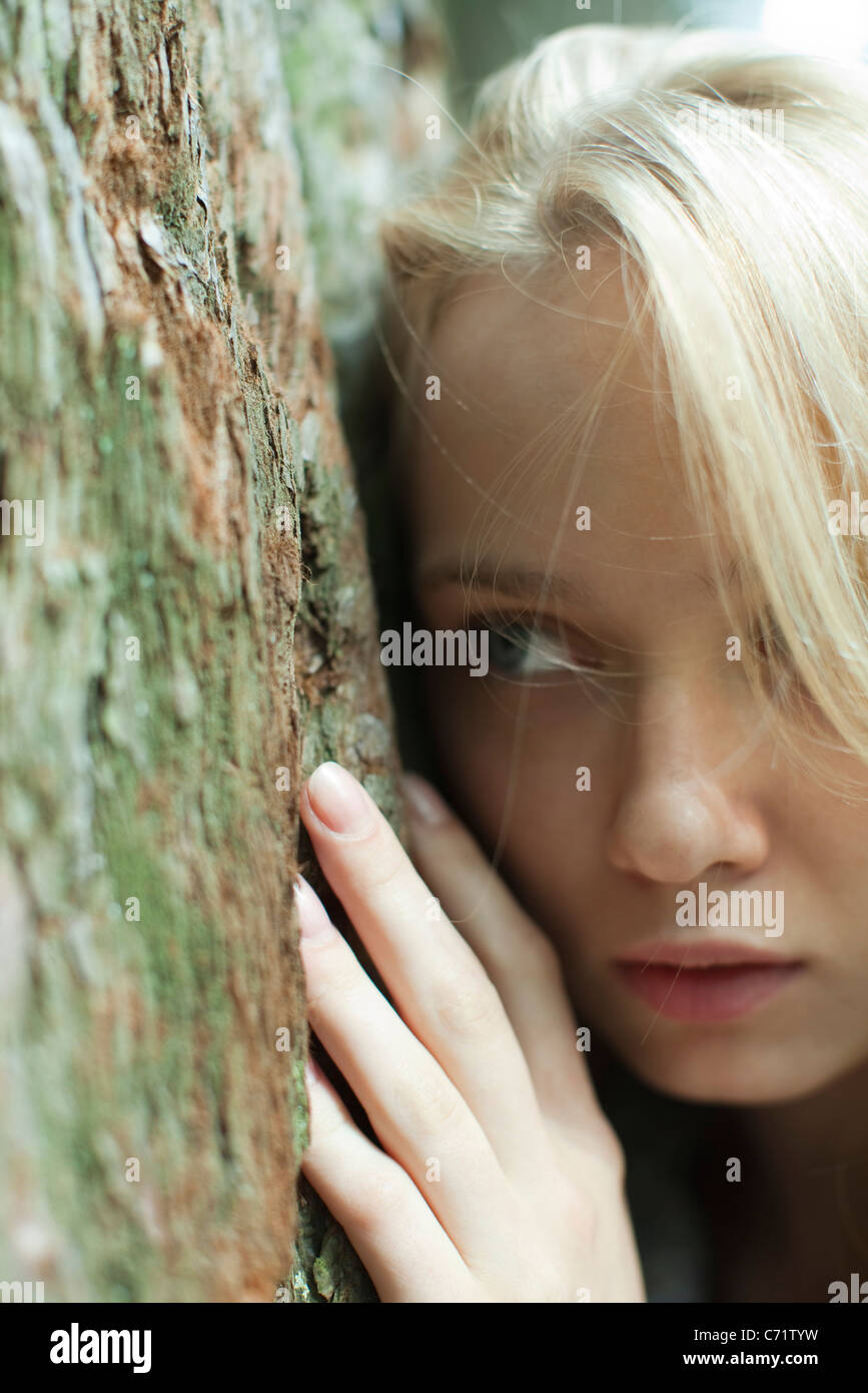 Young woman leaning against tree trunk - Stock Image