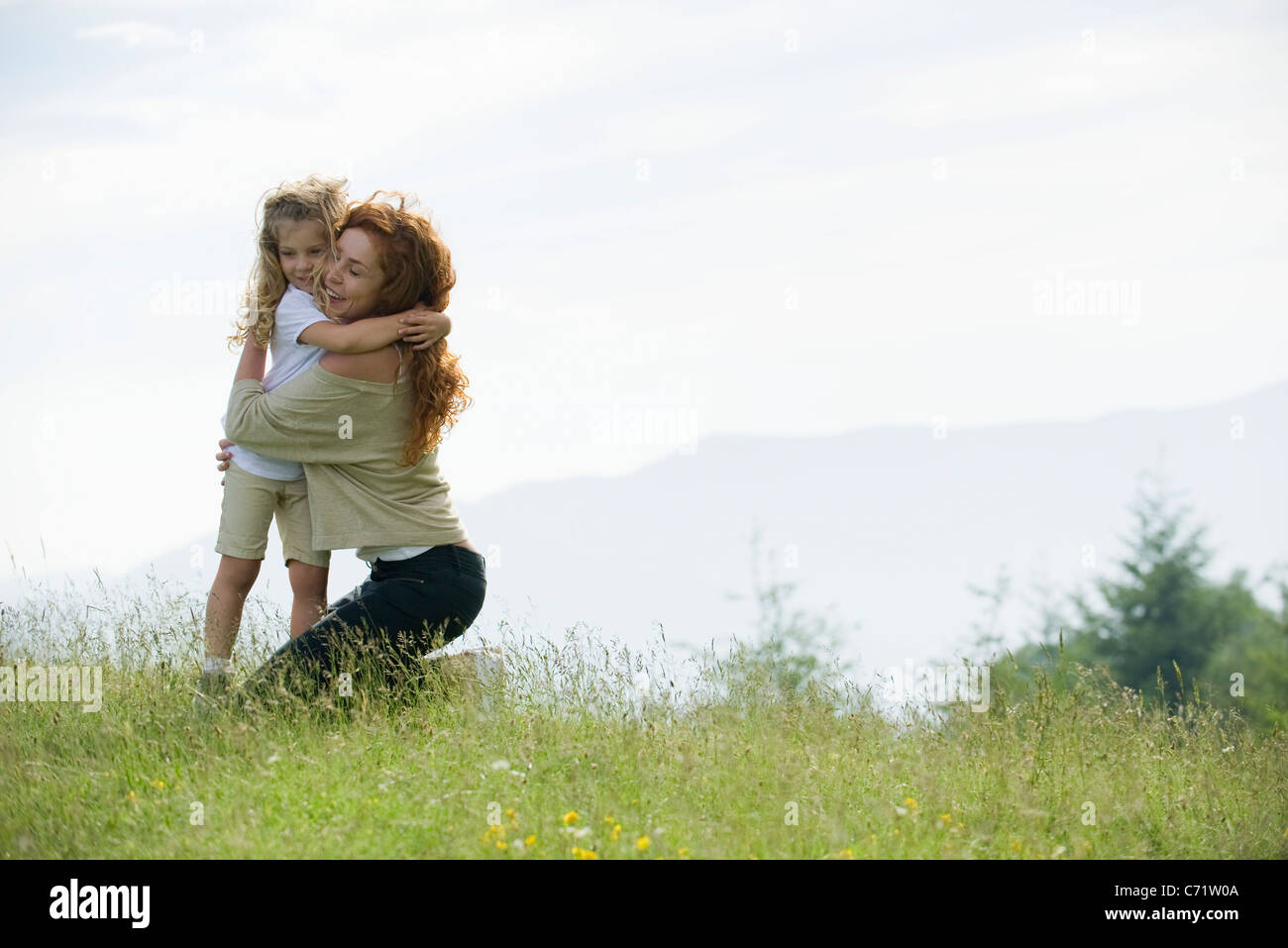Mother and young daughter embracing in meadow - Stock Image