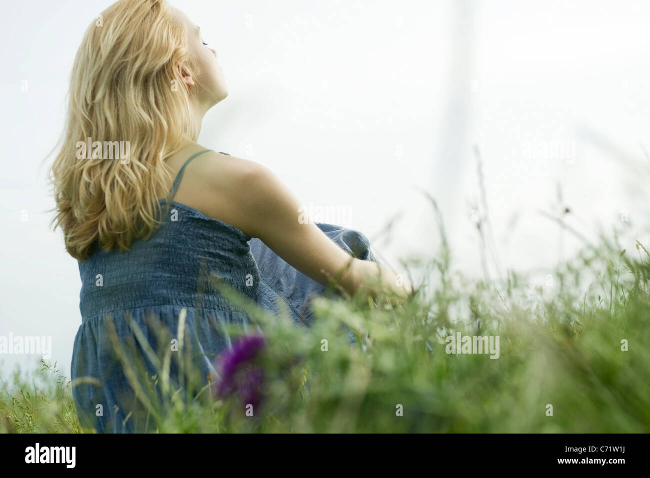 Young woman sitting in grass, daydreaming - Stock Image