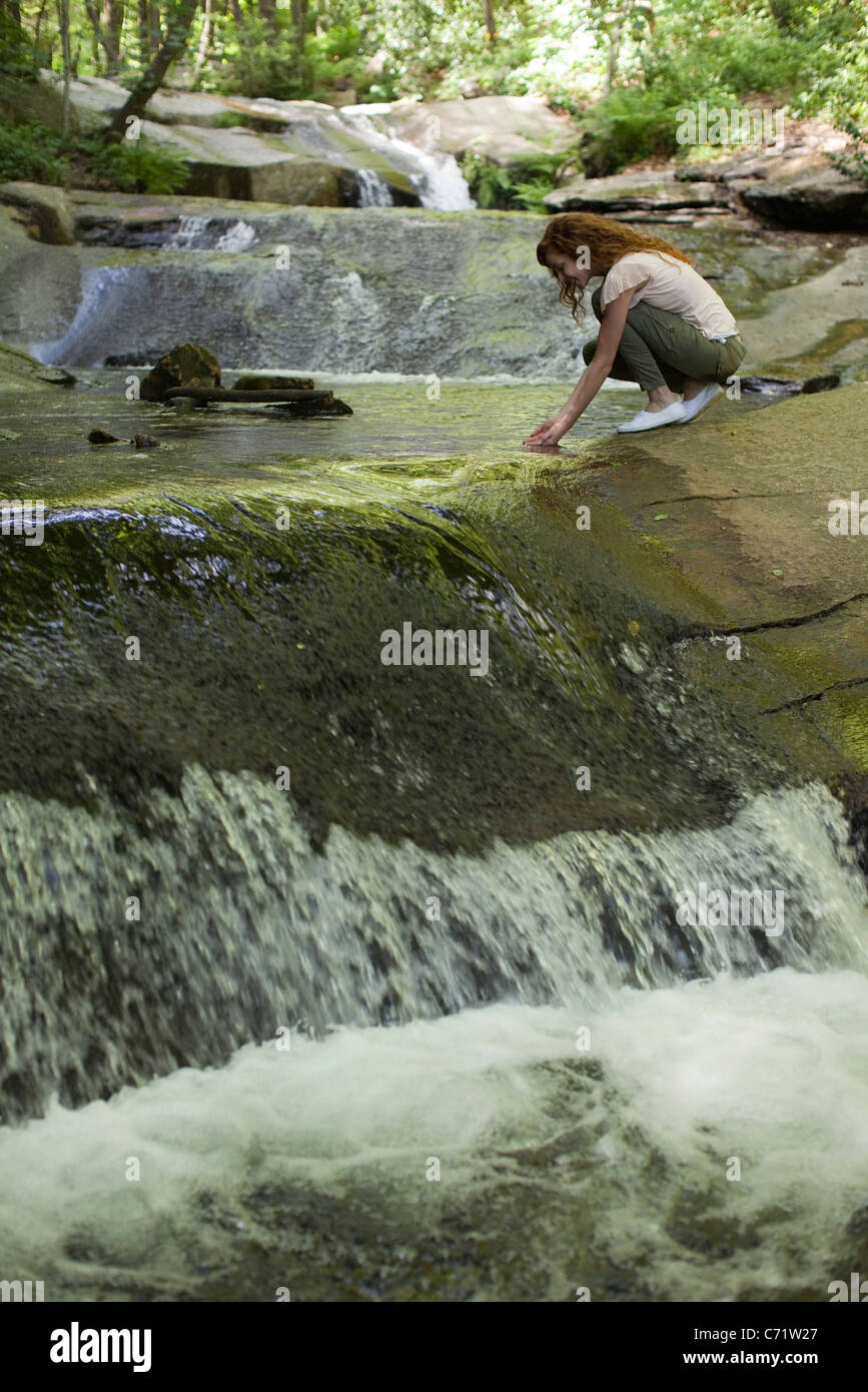 Woman crouching beside cascading stream, dipping hands in water - Stock Image