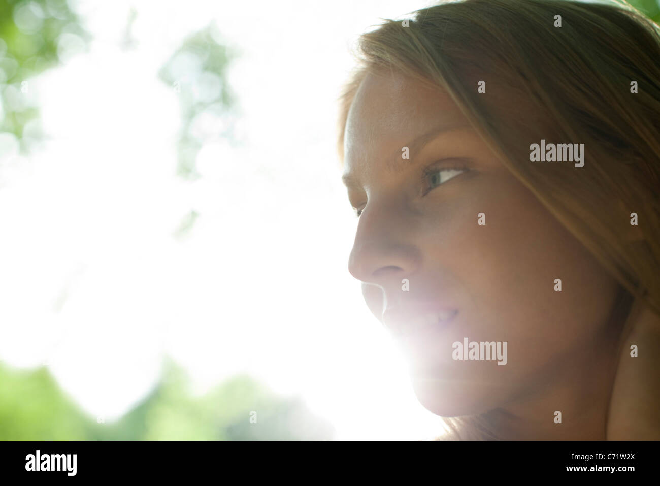 Young woman outdoors, looking away in thought - Stock Image