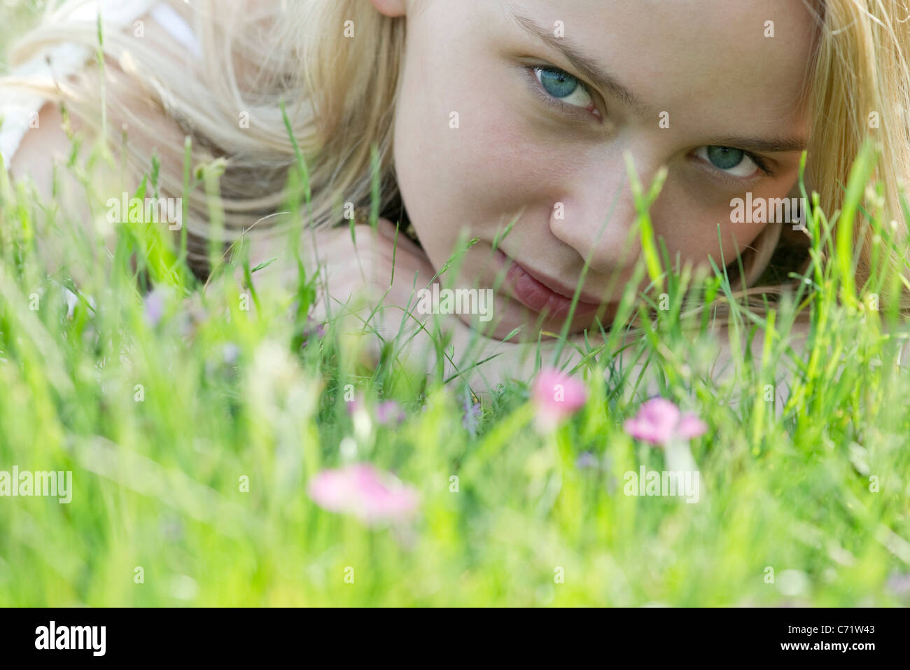 Young woman lying in grass, portrait - Stock Image