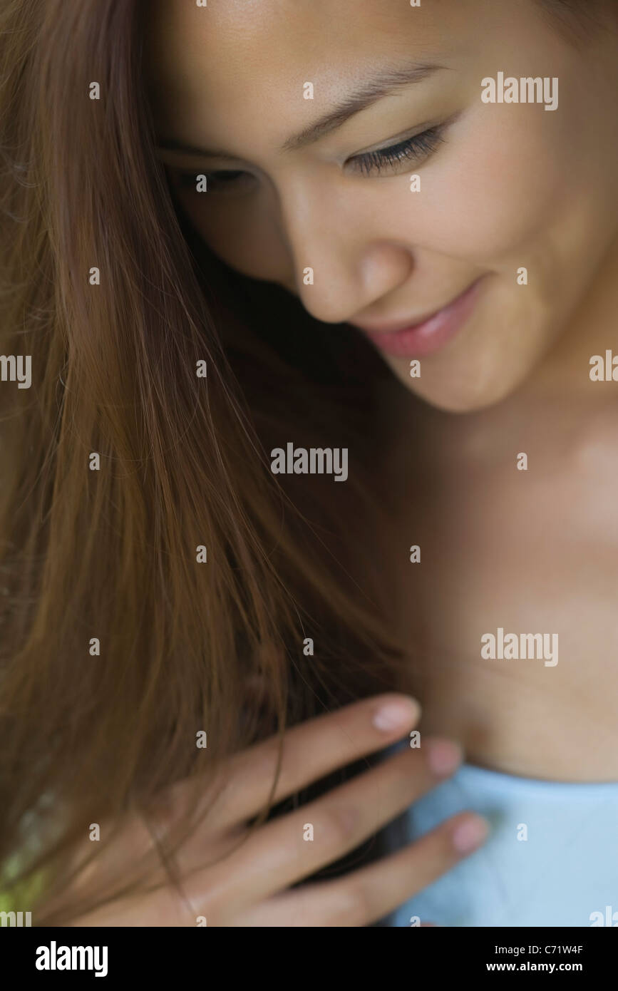 Smiling young woman looking down - Stock Image