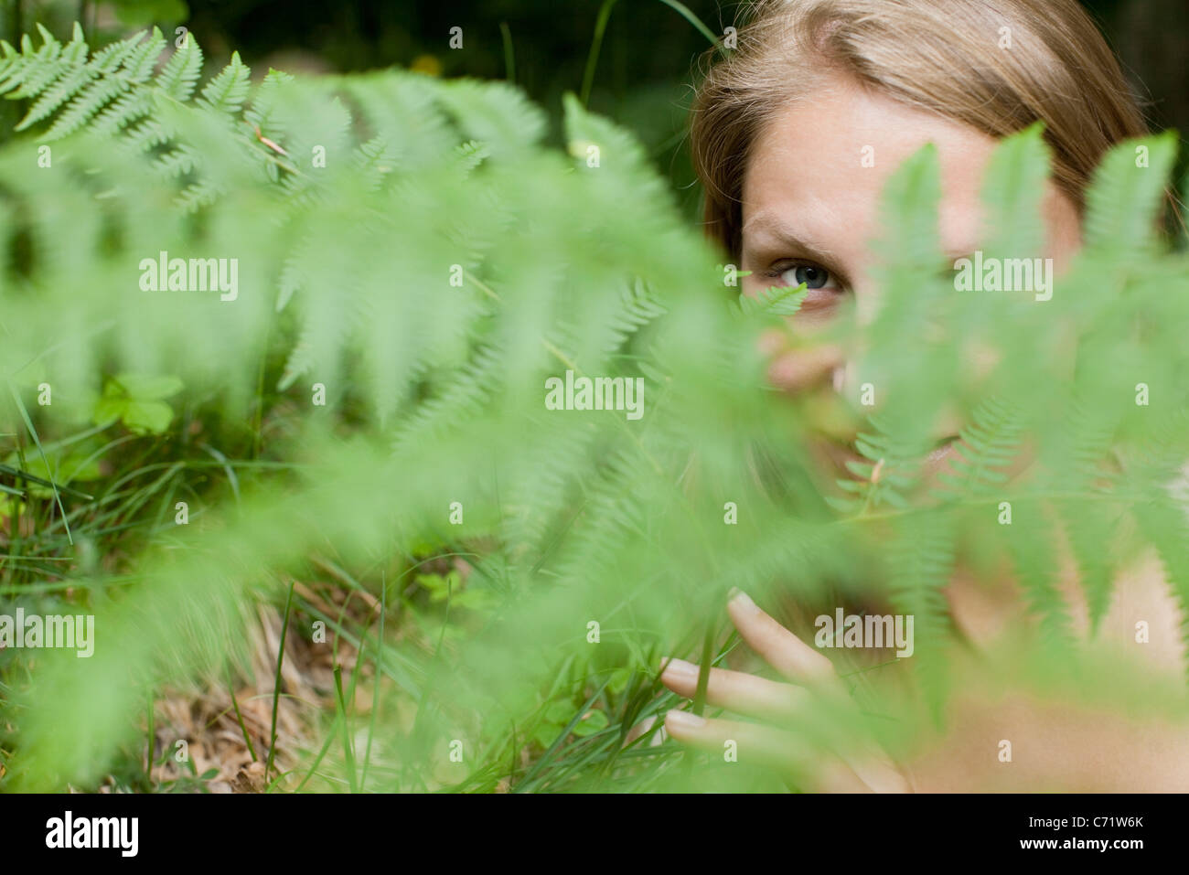 Woman peeking through fern frond, portrait - Stock Image