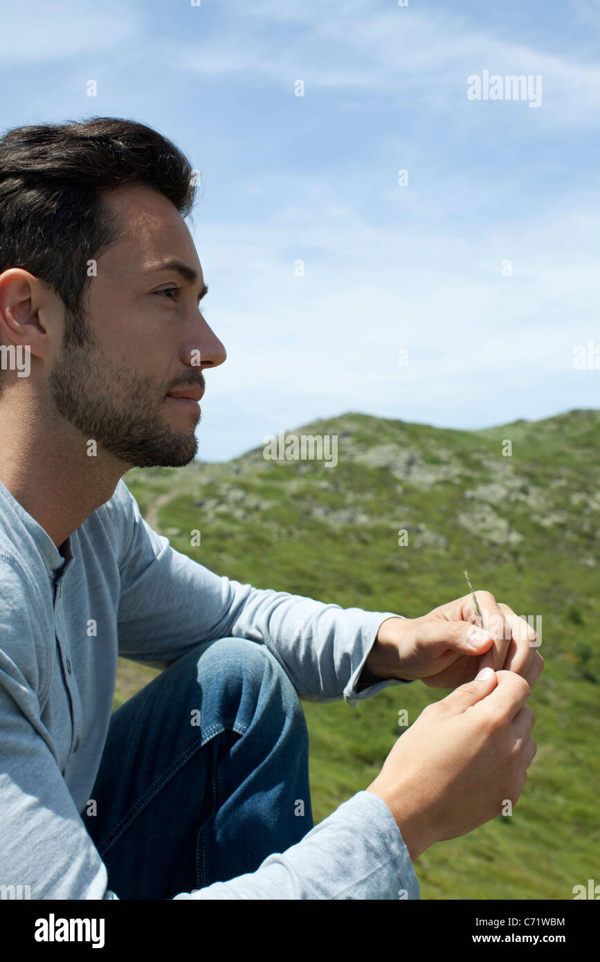 Man sitting outdoors, looking away in thought - Stock Image