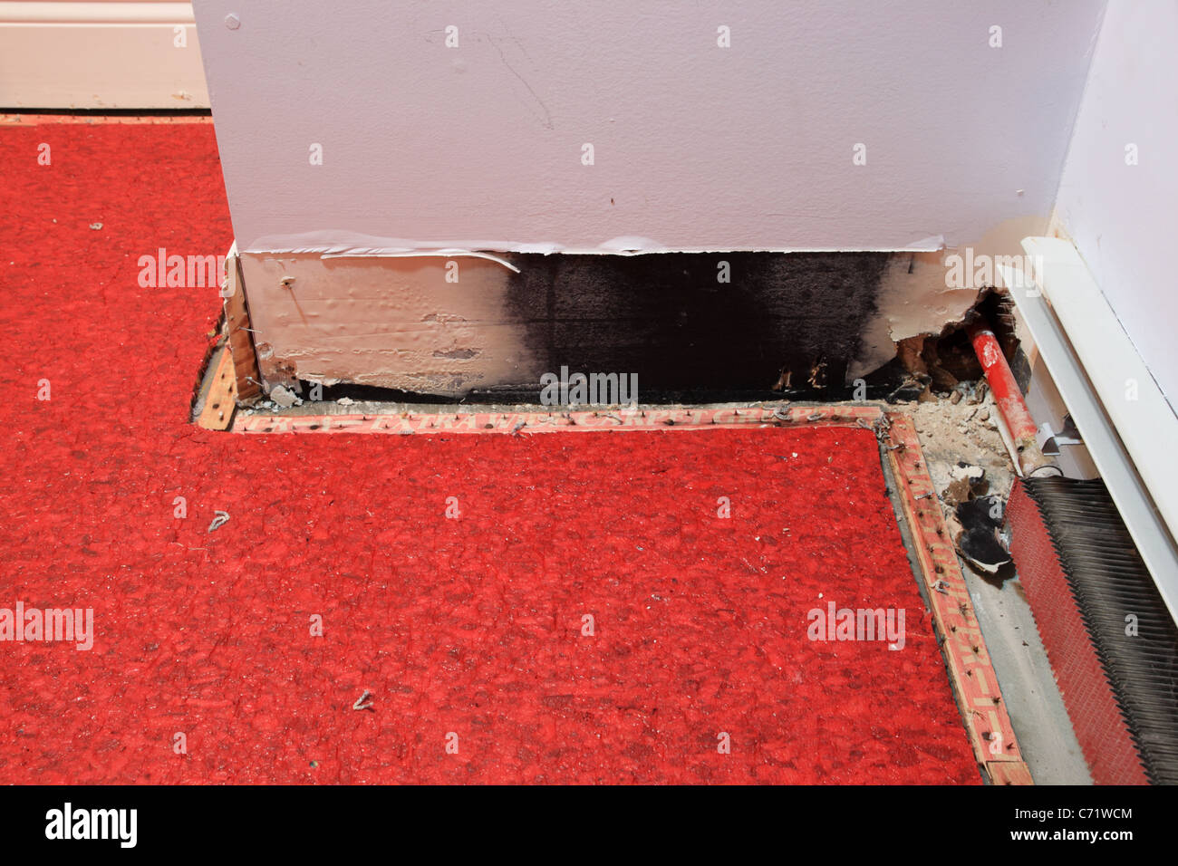 a water damaged wall from leaking pipe with carpet pulled back to dry - Stock Image