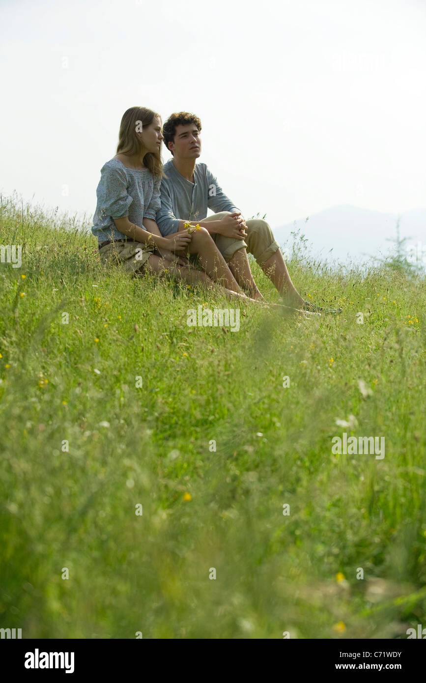 Couple sitting on meadow looking at view Stock Photo