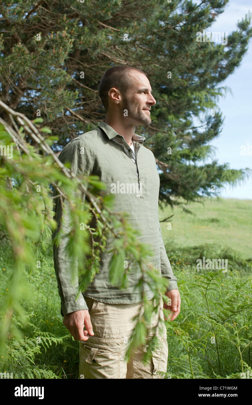 Man standing beside tree, looking at view - Stock Image