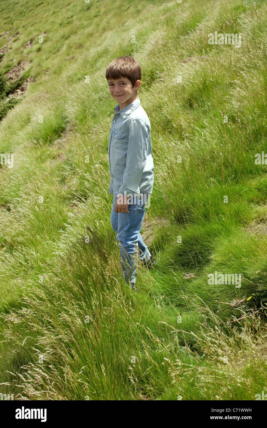 Boy walking on hillside, portrait - Stock Image