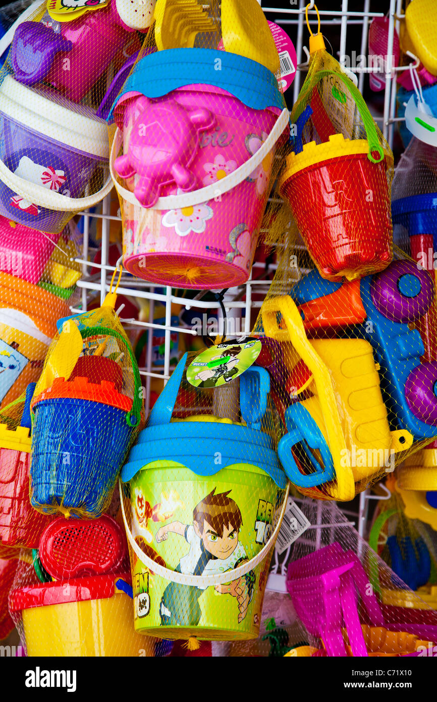 Brightly coloured children's plastic beach toys on display outside a seaside shop. - Stock Image