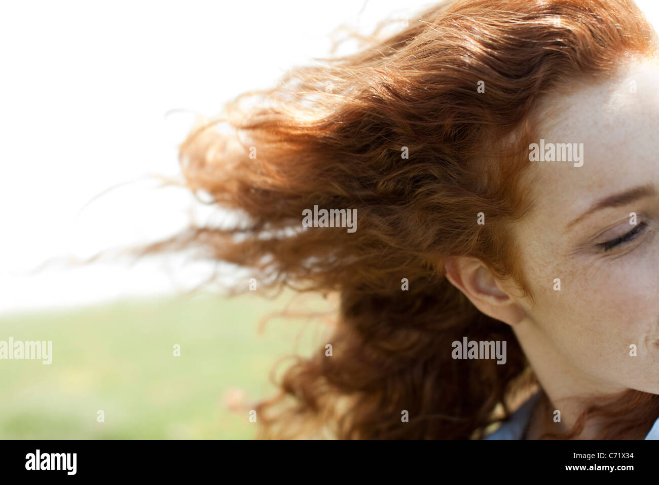 Redheaded woman with hair blowing in wind - Stock Image