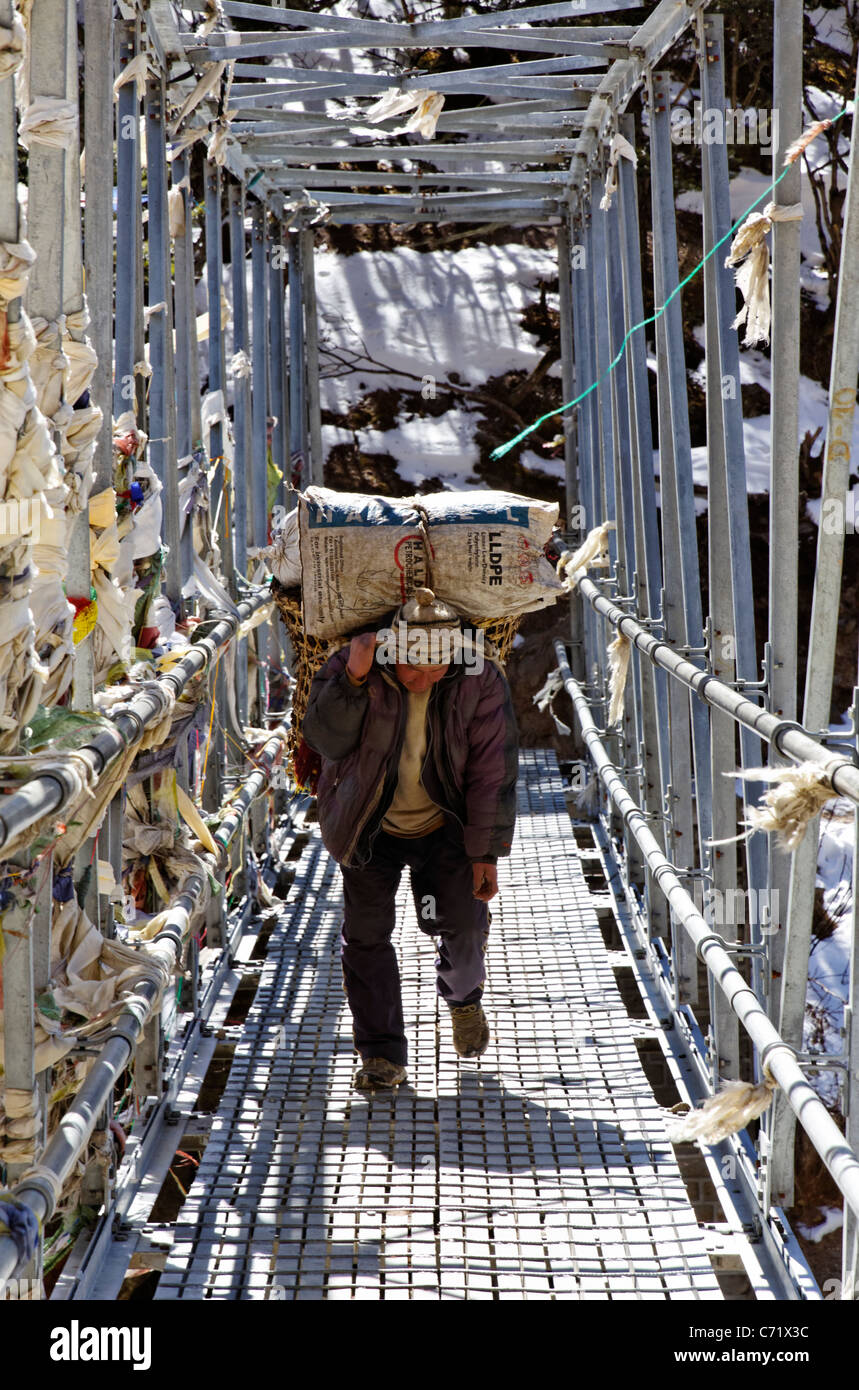 Man carrying heavy load over a footbridge, Everest Region, Nepal - Stock Image