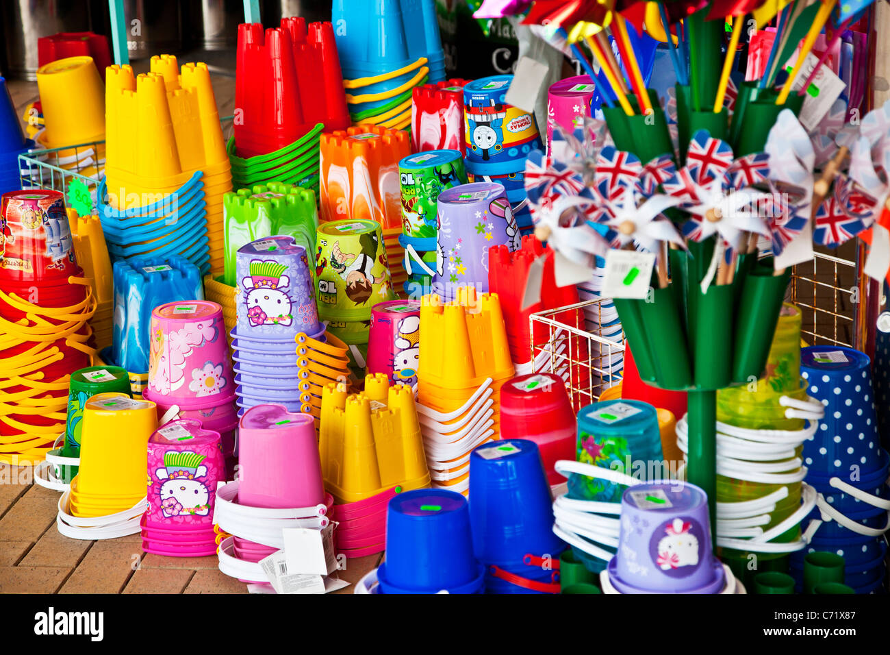 Brightly coloured children's plastic beach toys and buckets on display outside a seaside shop. - Stock Image