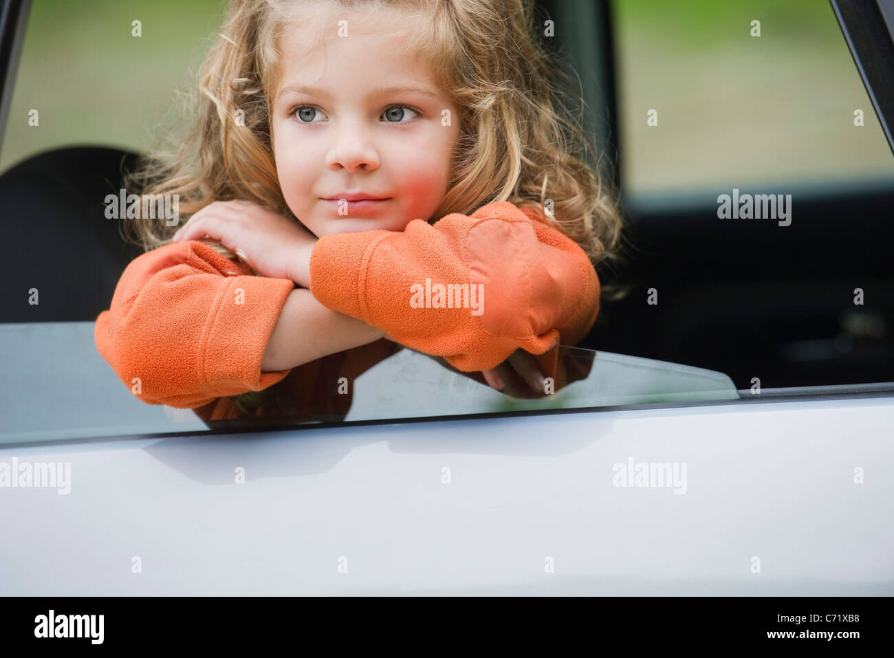 Little girl looking out car window, portrait - Stock Image