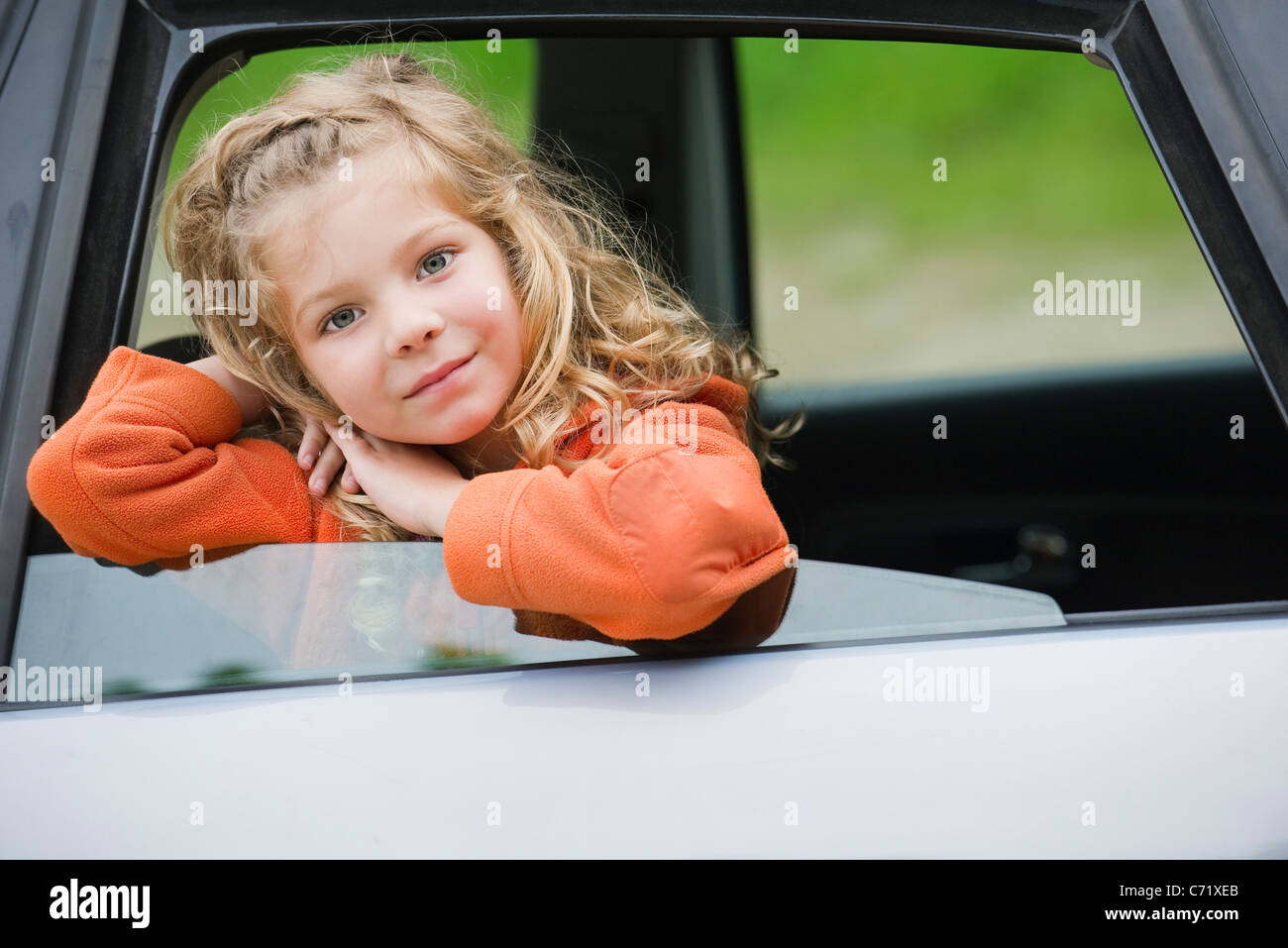 Little girl leaning out car window, portrait Stock Photo