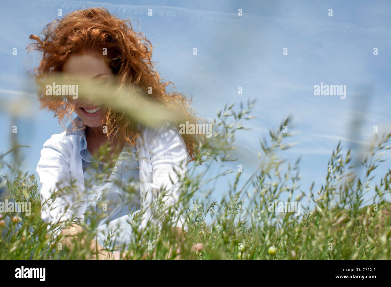 Redheaded woman in grass Stock Photo