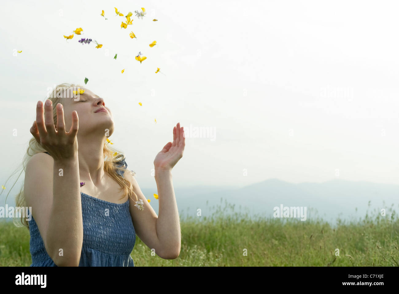 Young woman in meadow, covered in wildflowers - Stock Image