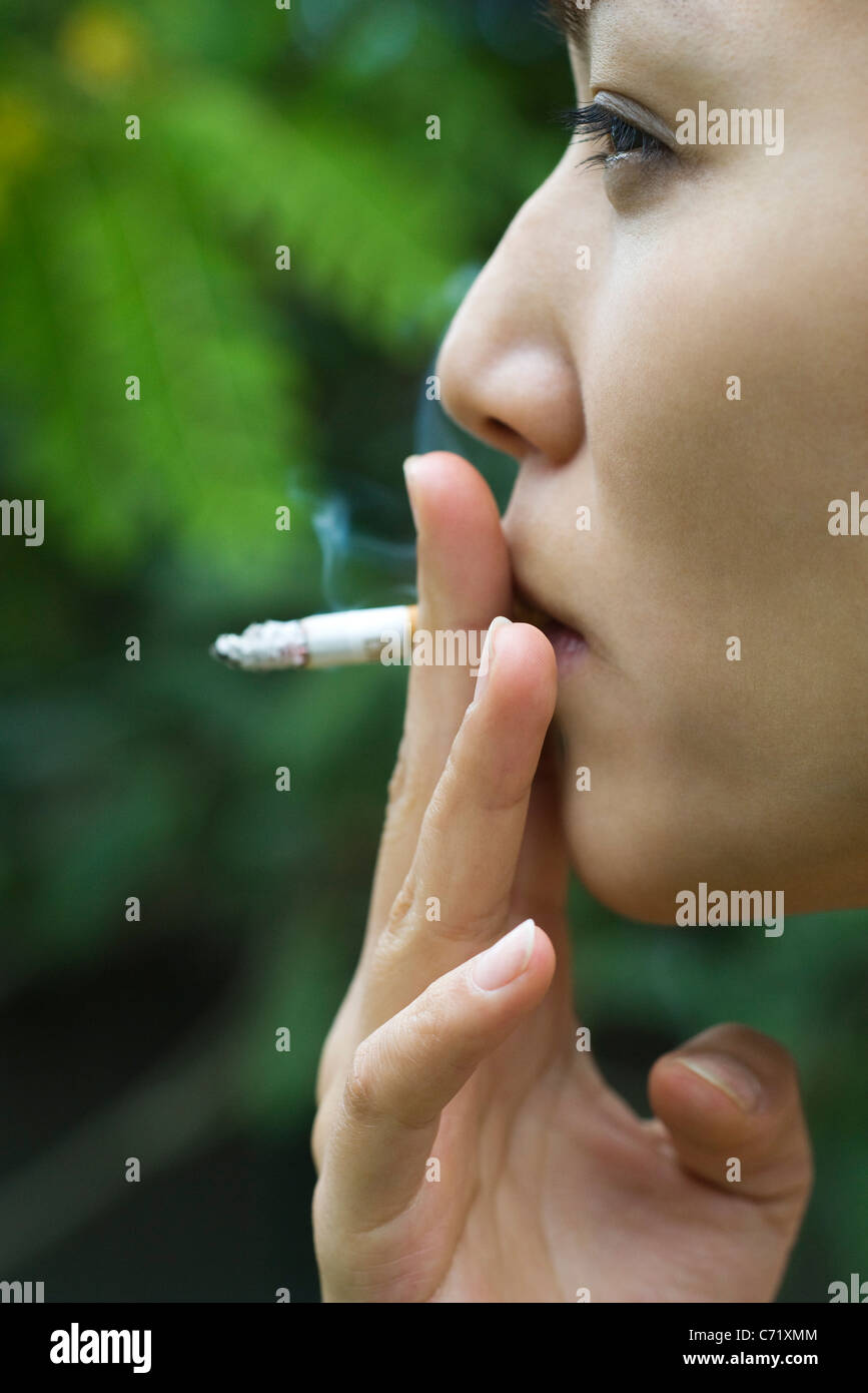 Young woman smoking outdoors, side view - Stock Image