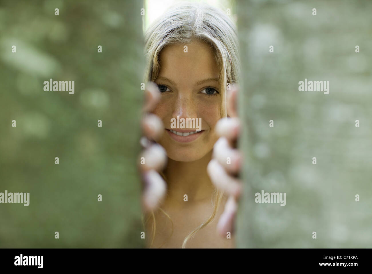 Young woman peering out from behind tree trunks - Stock Image