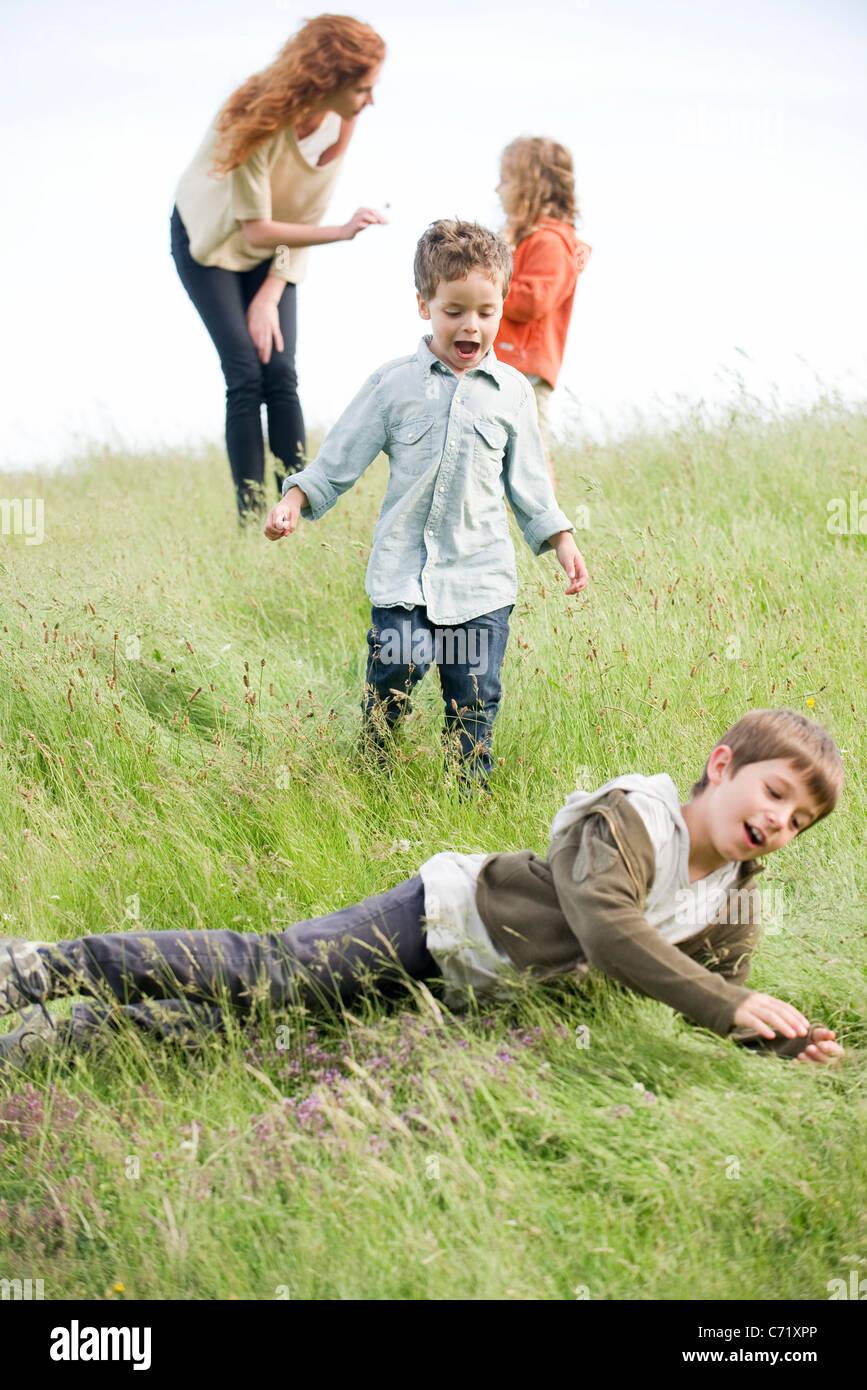 Boys playing in field, mother and sister in background Stock Photo