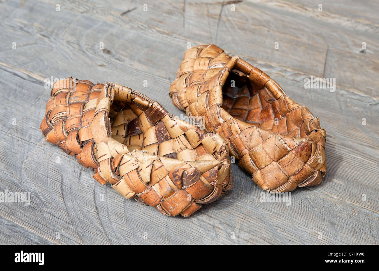 Rural still life. Russian traditional bast shoes on background of boards. - Stock Image