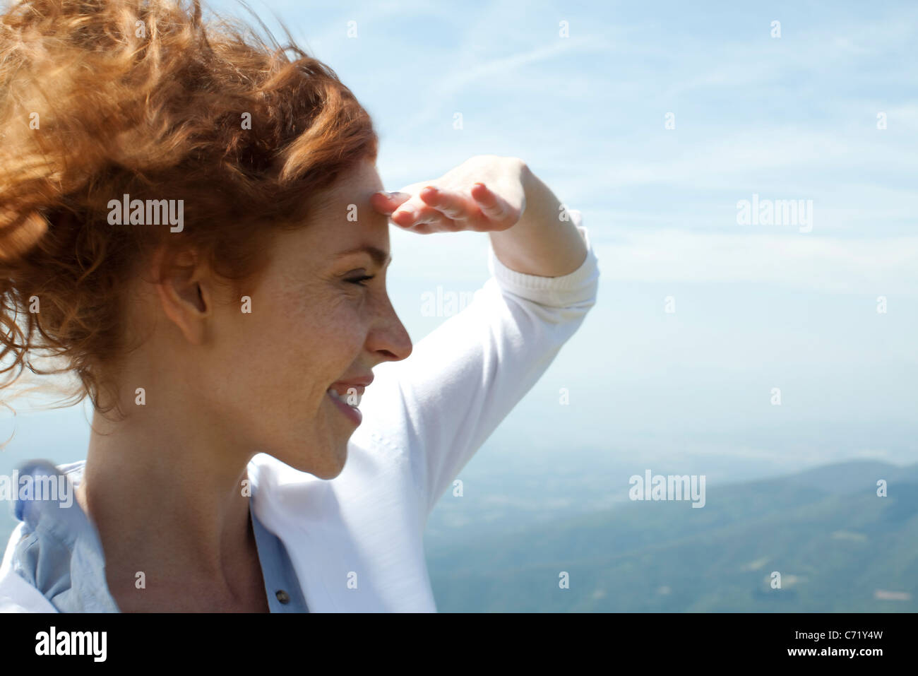 Woman looking at view, shading eyes with hand - Stock Image