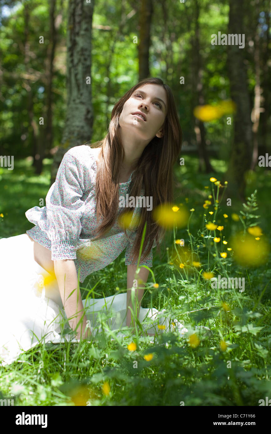 Young woman sitting in forest - Stock Image