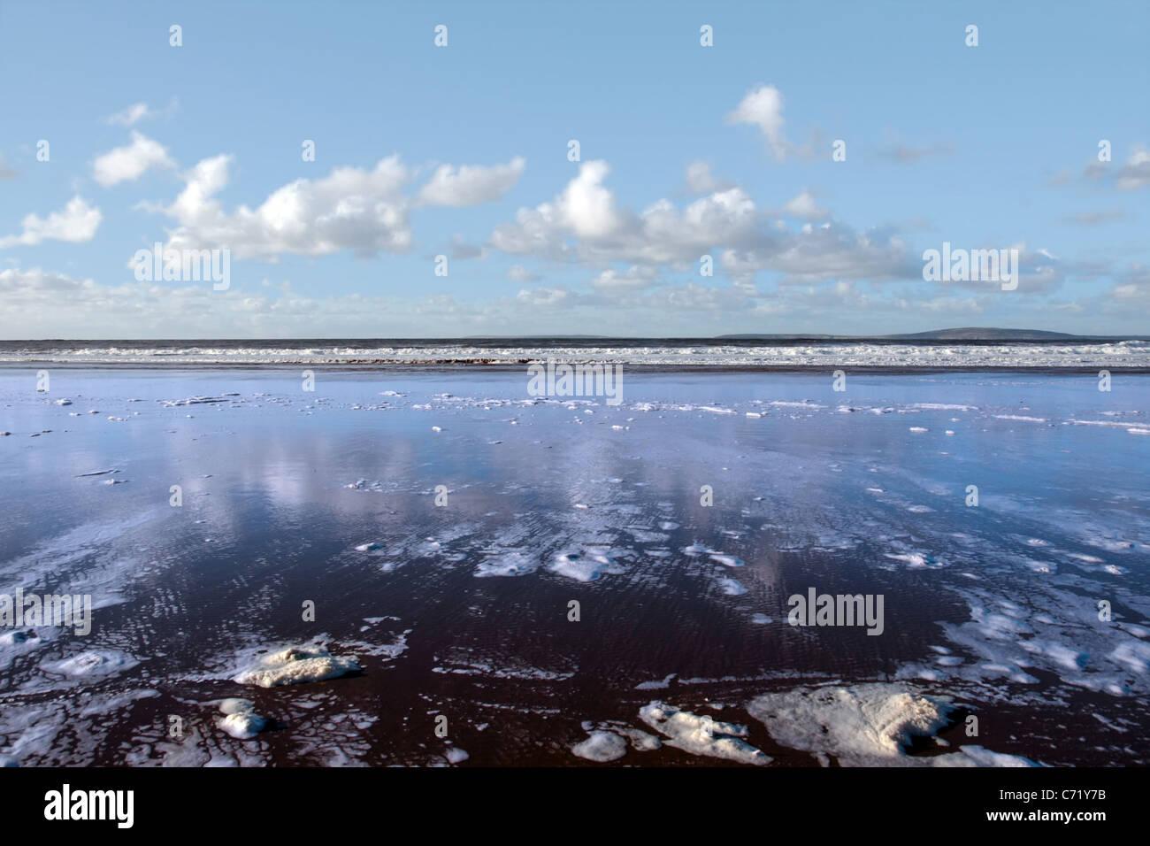 the waves with reflection crashing in on ballybunion beach ireland - Stock Image