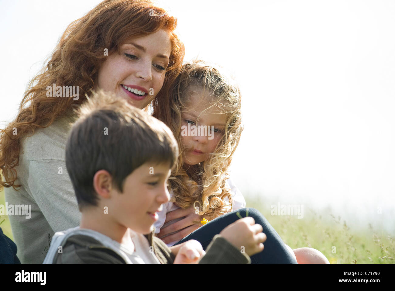 Mother and two children relaxing together outdoors - Stock Image