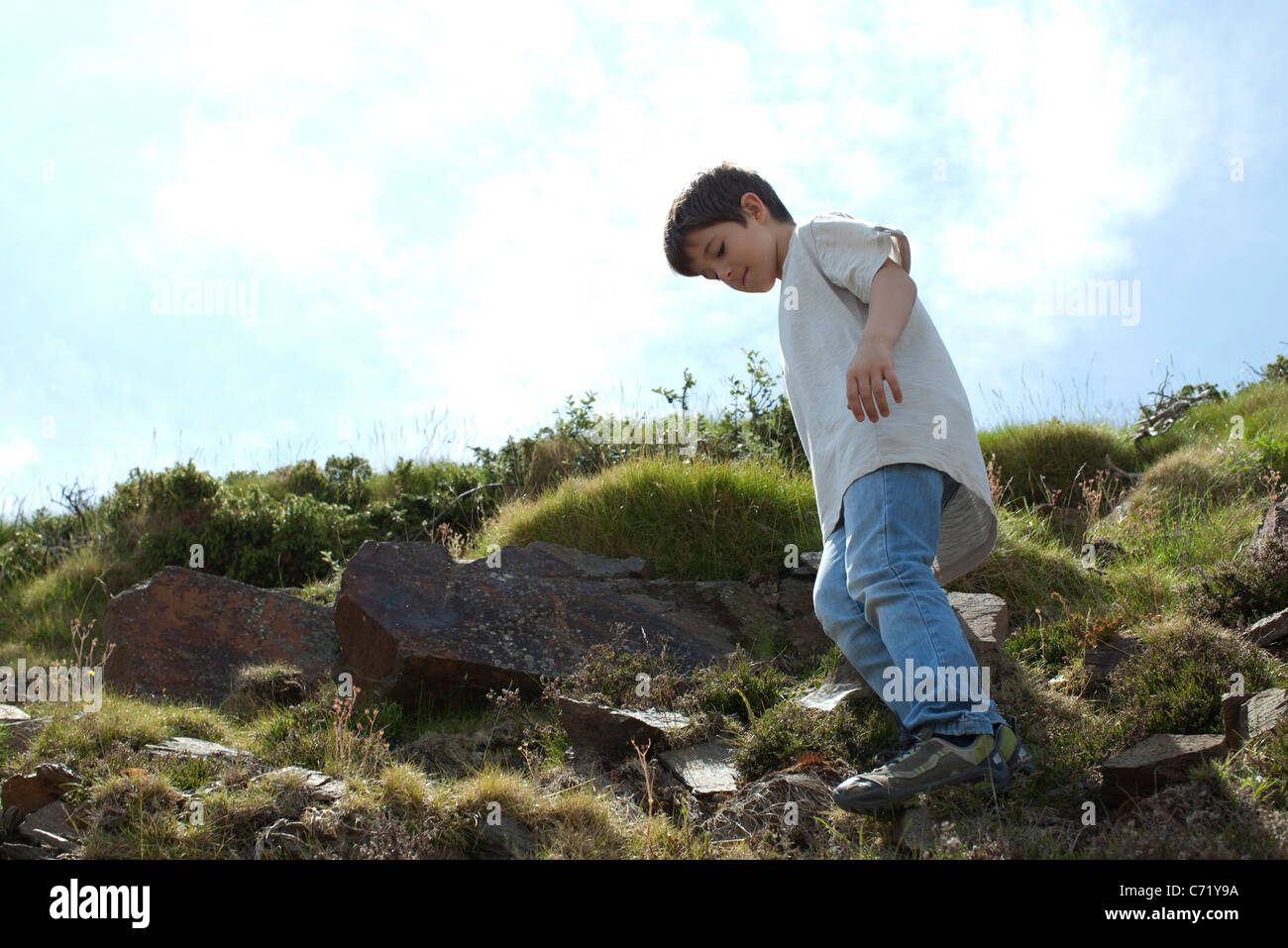 Boy standing on rocky hillside, low angle view - Stock Image