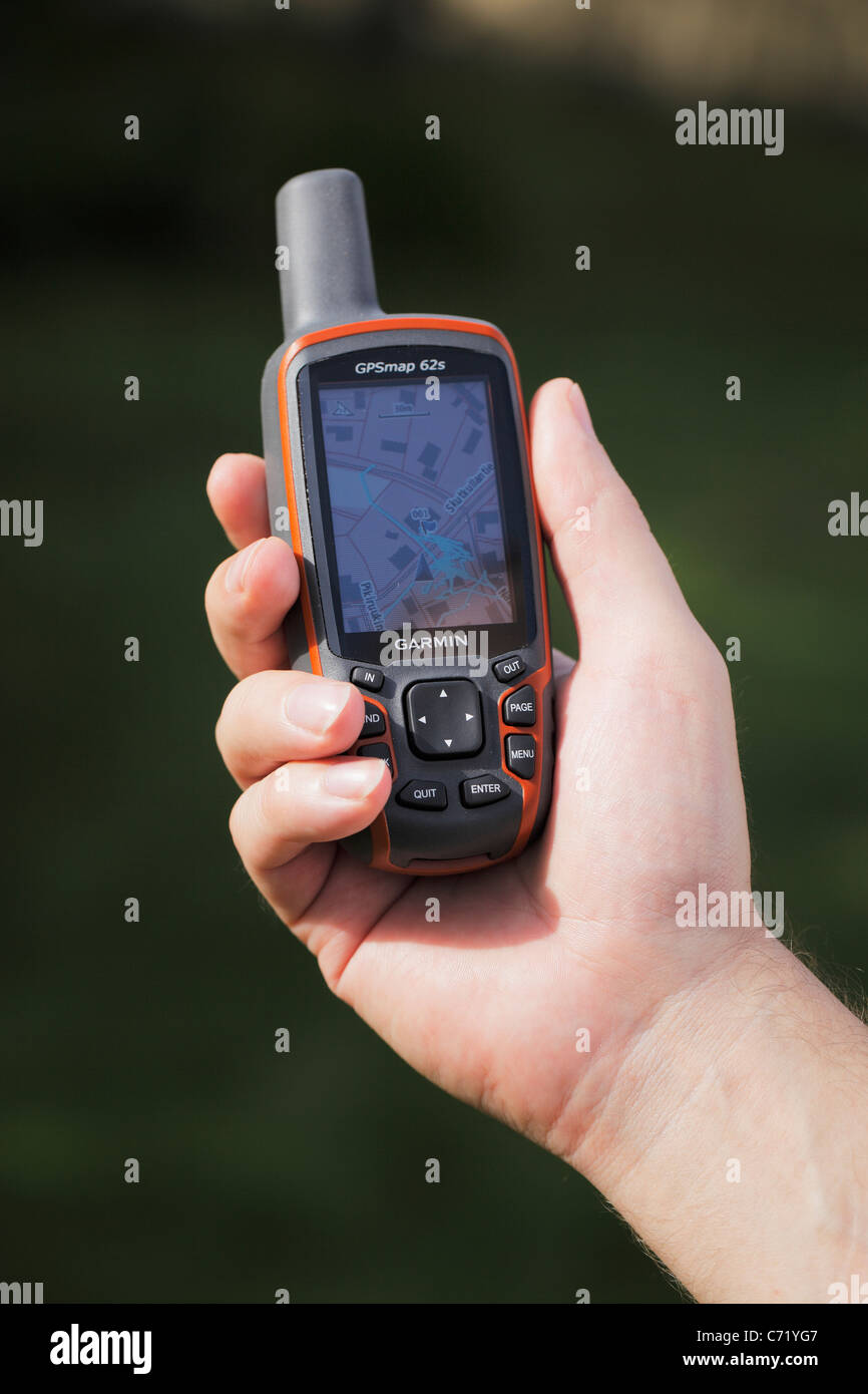 Man holding a GPS receiver in his hand. - Stock Image