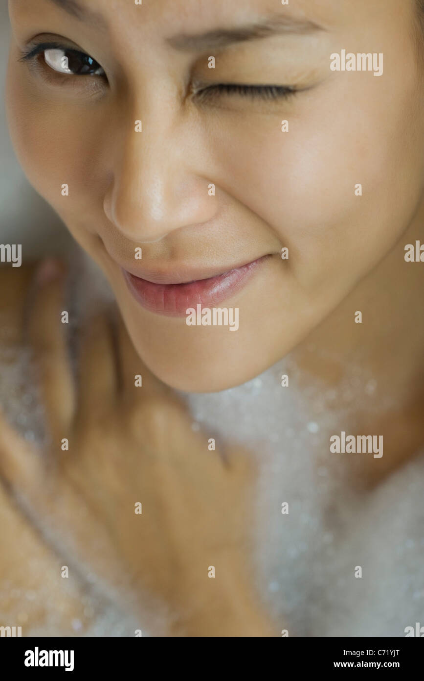 Young woman taking bubble bath, winking, high angle view Stock Photo
