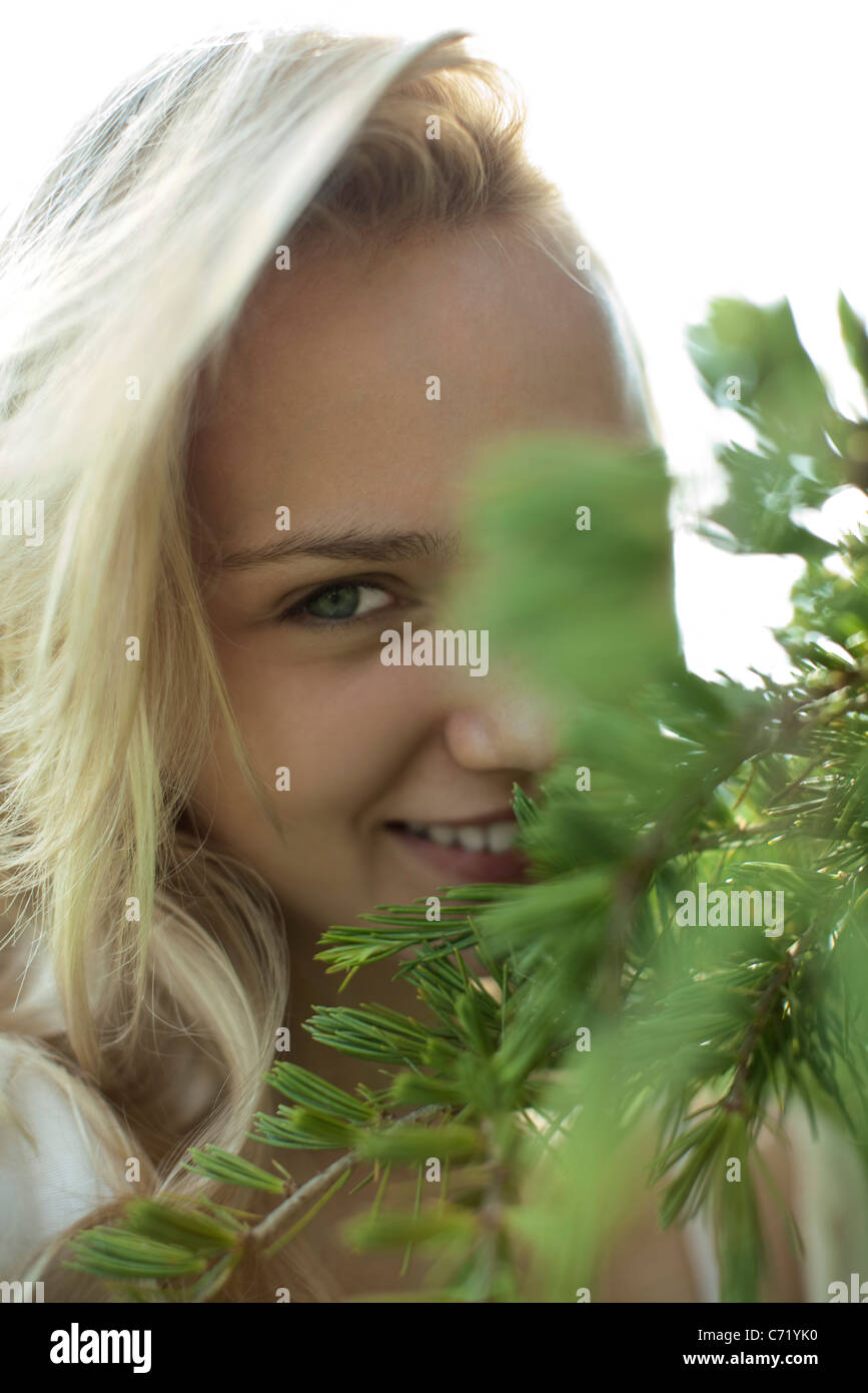 Smiling young woman behind tree branches, cropped - Stock Image