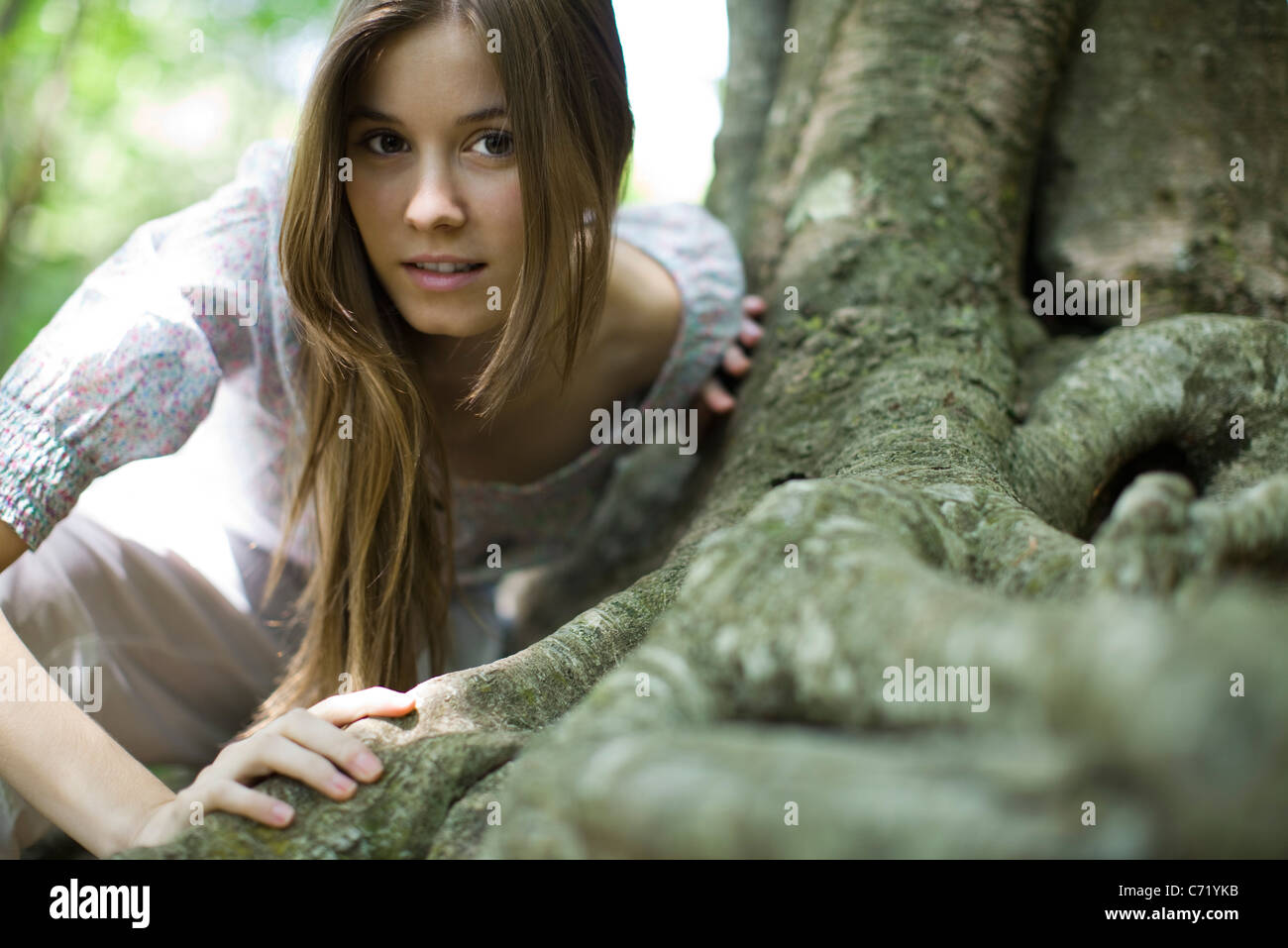 Young woman leaning on roots of tree - Stock Image