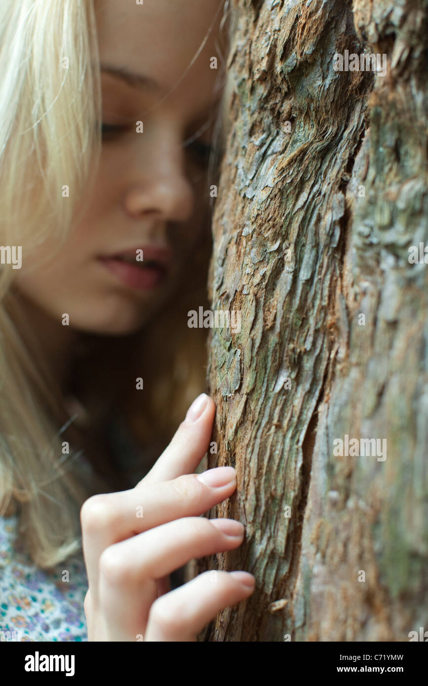 Young woman touching tree trunk - Stock Image