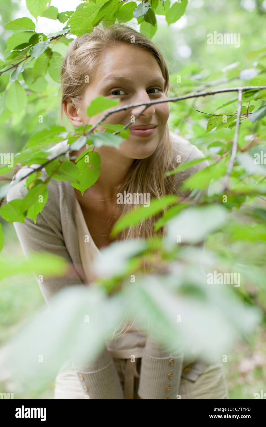 Young woman behind tree branches - Stock Image