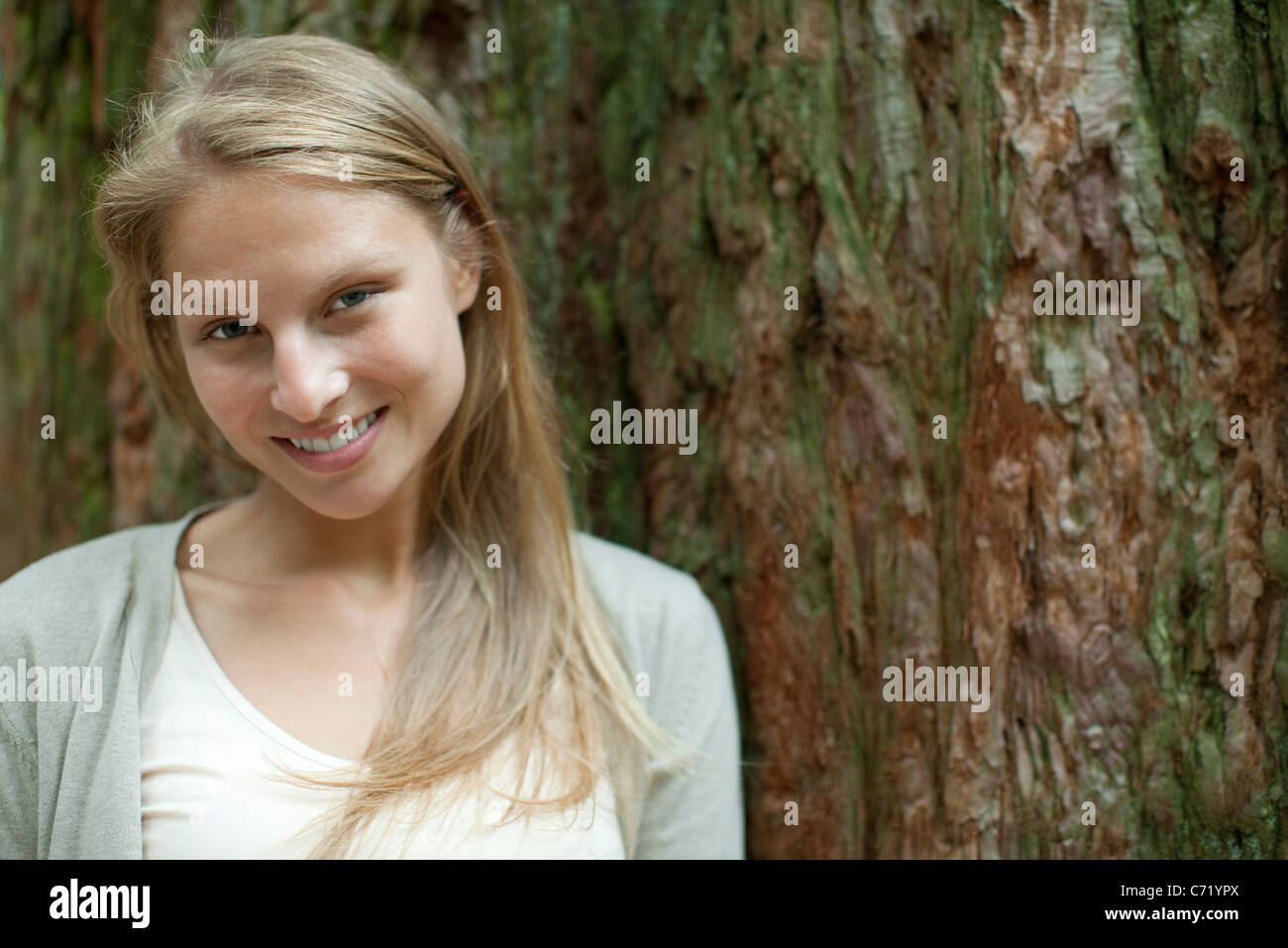 Young woman leaning against tree trunk, portrait - Stock Image