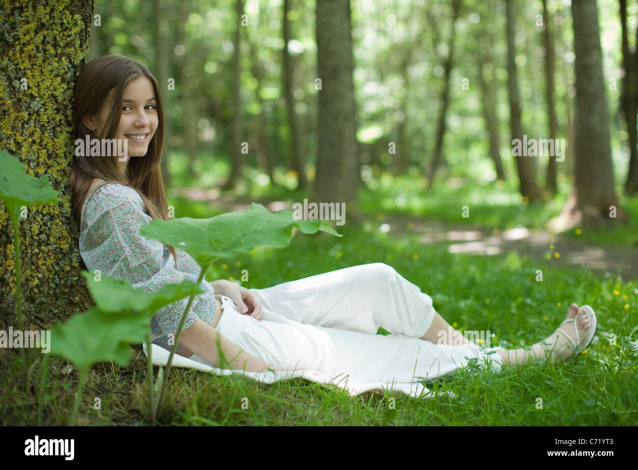 Young woman sitting against tree in woods, portrait - Stock Image