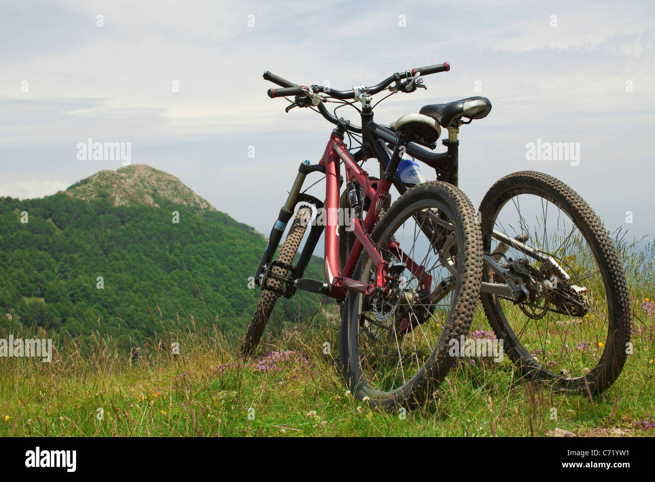 Two bicycles leaning against each other on hilltop - Stock Image