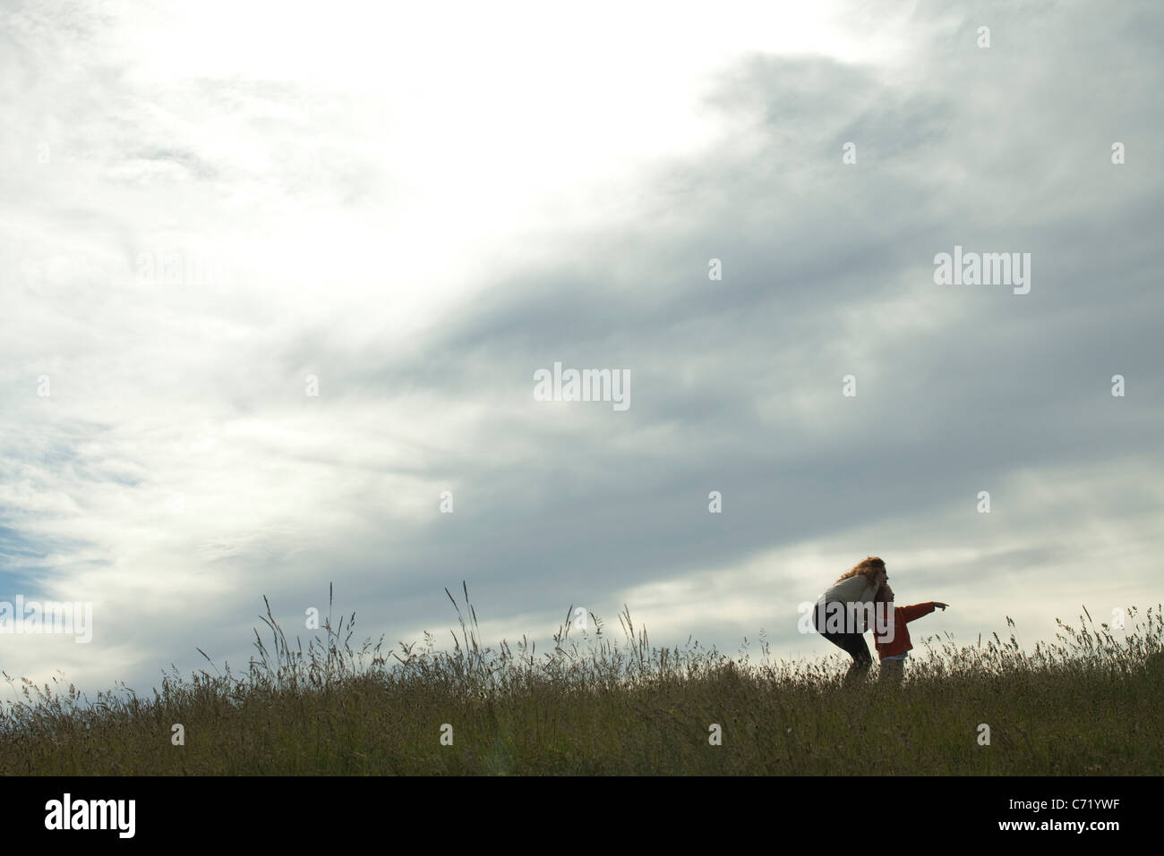 Mother and child standing in meadow, looking at something in the distance - Stock Image