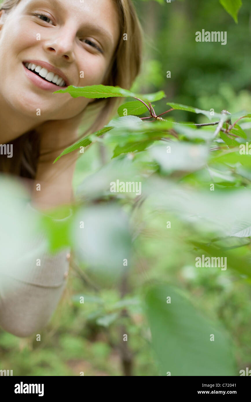 Woman smiling at camera from behind foliage, portrait - Stock Image