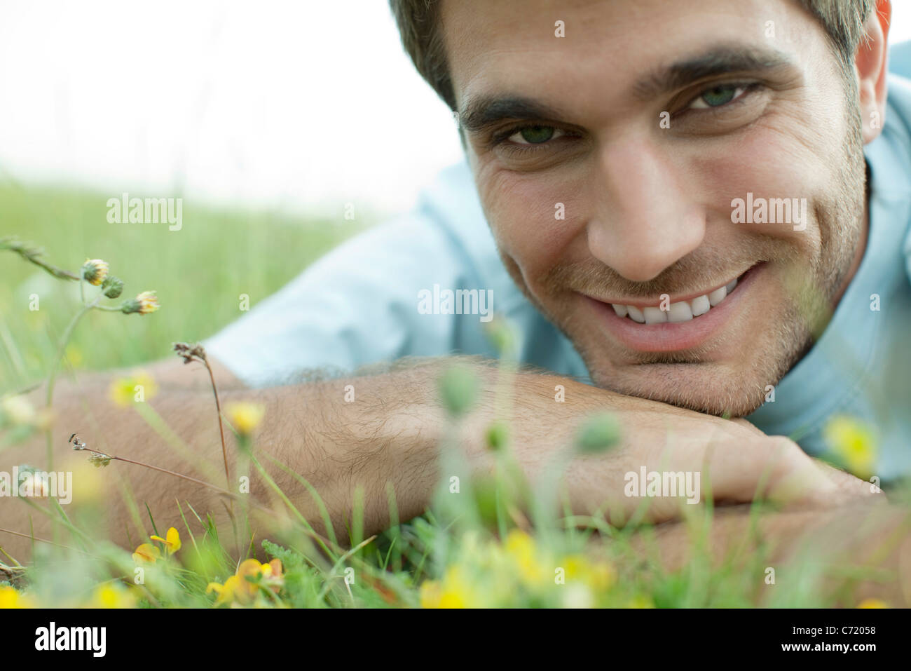 Man relaxing on meadow, cropped - Stock Image