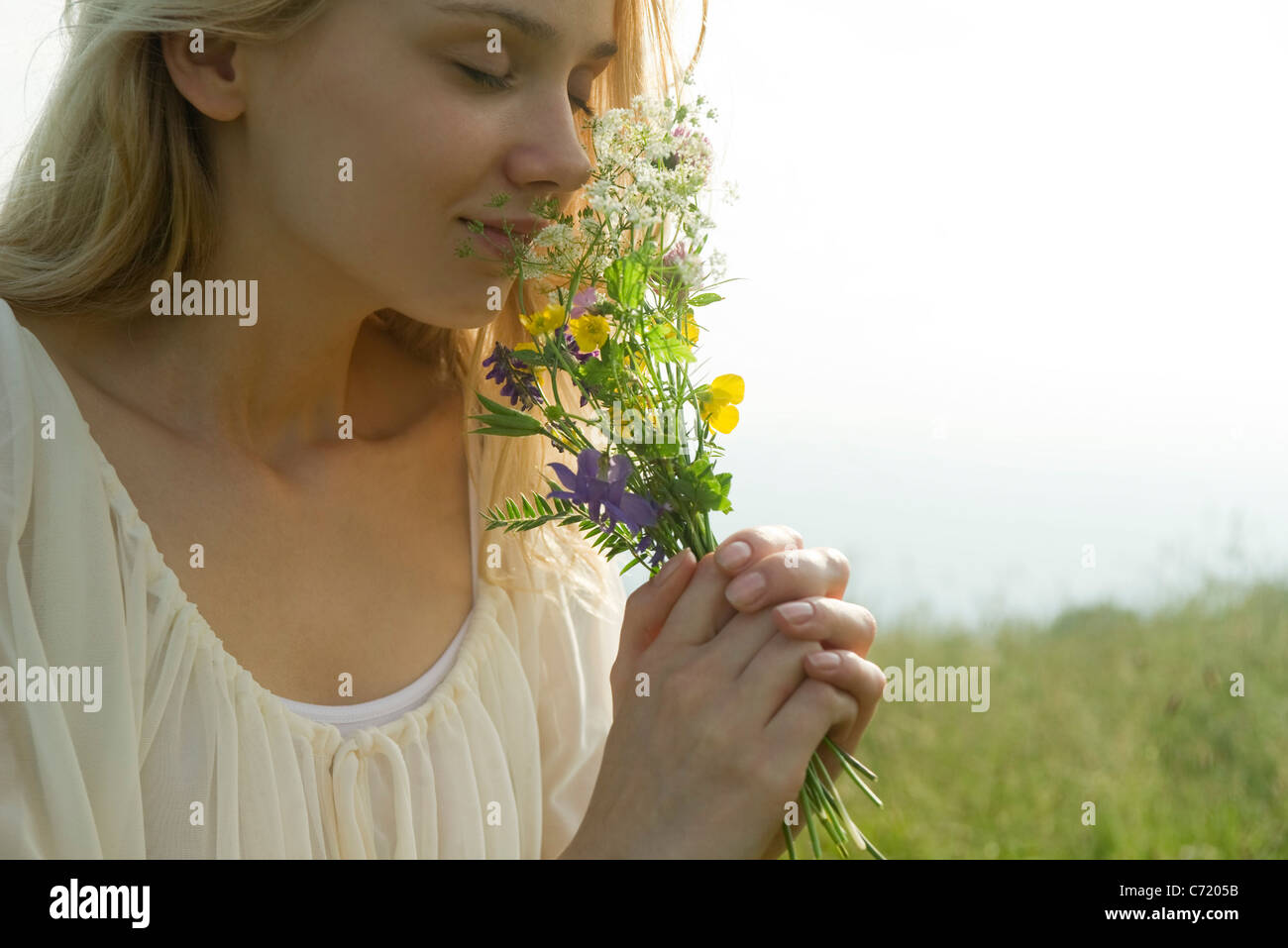 Young woman smelling bouquet of wildflowers, cropped - Stock Image