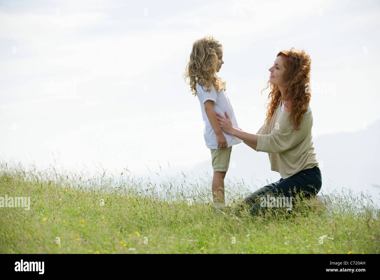 Mother comforting young daughter outdoors - Stock Image